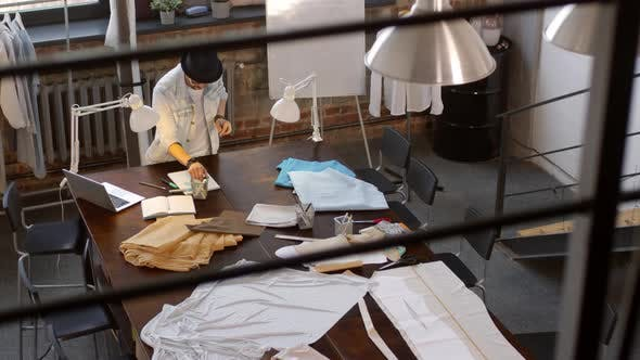 Thumbnail for Male Fashion Designer Drawing Look in Album in Sewing Studio