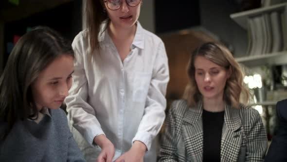 Thumbnail for Team von kreativen Designern schauen auf das Projektmagazin, reden über sie, sitzen zusammen