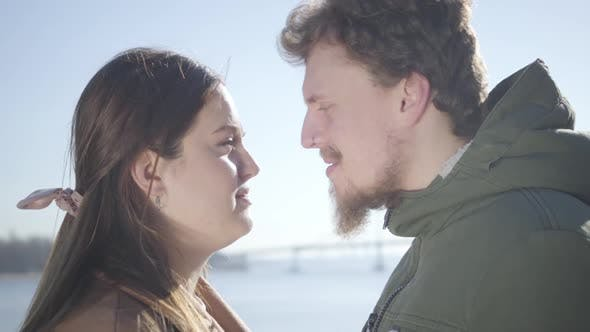 Cover Image for Close-up of Smiling Caucasian Man with Nose Ring and Chubby Brunette Woman Rubbing Noses on River
