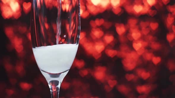 Thumbnail for Champagne Is Poured Into a Glass on a Red Background with Many Hearts, Close Up.