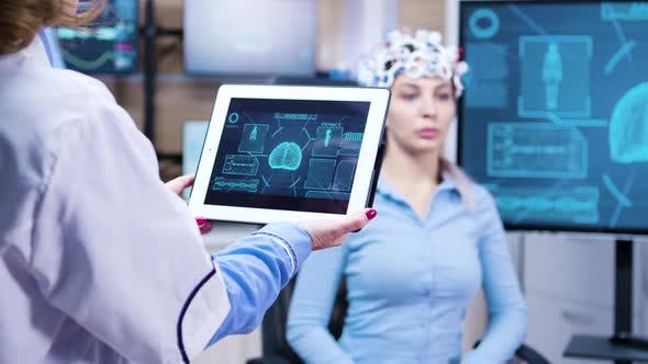 Thumbnail for Middle Age Female Doctor Holding Tablet with Patient Brain Activity