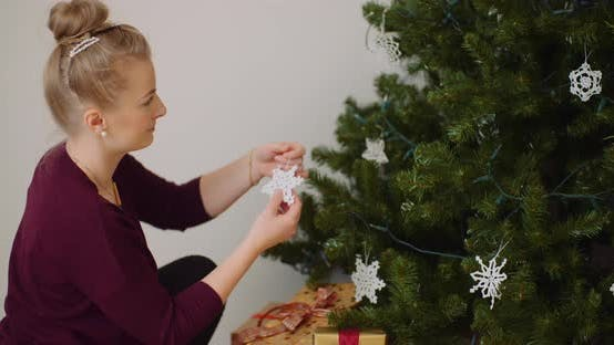 Thumbnail for Woman Decorating Christmas Tree With Ornaments And Lights
