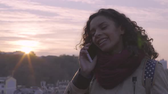 Thumbnail for Cheerful Young Lady Smiling and Laughing During Phone Conversation, City Sunset