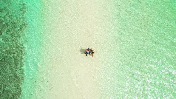 Cover Image for Happy Couple, Man and Woman Stand in Shallow Water in the Turquoise Water of Snake Island in El Nido