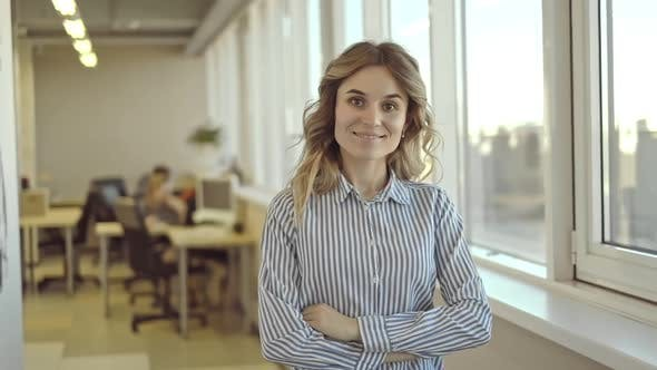 Confident Woman Standing in Office Gives Kind Friendly Look at Camera Smiles Irrl