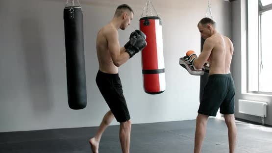 The Kickboxer is Practising His Middle Kick with Trainer in Slow Motion in the Gym Mixed Martial