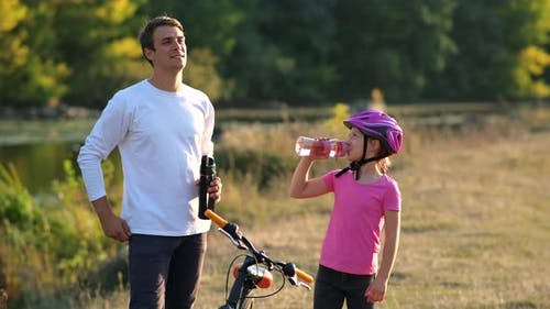 Dad and a little girl in a Bicycle helmet drink clean water near the bike on the river Bank.