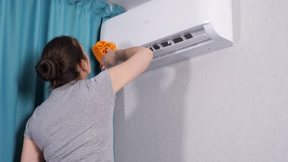 Woman Sprays Water on Cloth and Cleans Air Conditioner