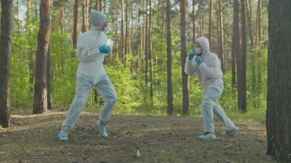 Men in Protective Suits Boxing in Nature