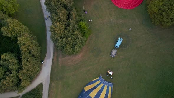 Thumbnail for Aerial View of Hot Air Balloons Prepare for an Summer Early Morning Flying in Park in Small European