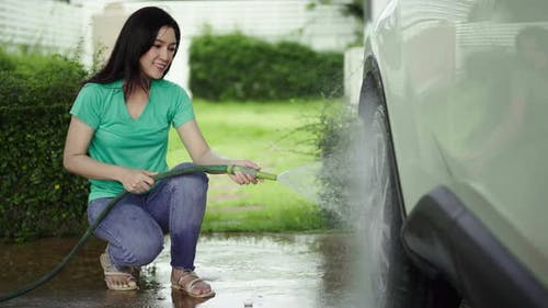 Young woman water spray her car wheel with water tube washing it