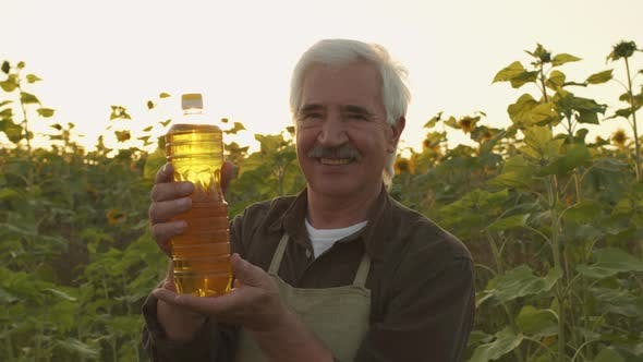 Portrait Of Farmer With Bottle Of Sunflower Oil