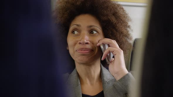 Afro American commuter on her way to work using smart phone
