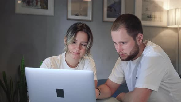 Serious young couple husband and wife pay bills online on website app doing paperwork planning
