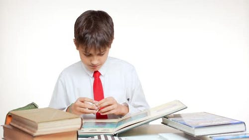 Young School Kid with Red Tie Sitting at Table with Books and Atlas Playing with Cube on White