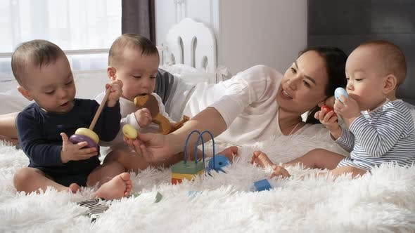 Relaxed Asian Mom Watching her Triplets Playing Together