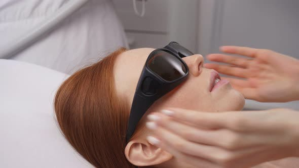 Beautiful Woman at a Cosmetologist's Appointment, Disinfects the Skin of the Face with Laser