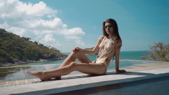Thumbnail for Dolly Shot of Beautiful Woman Resting on the Edge of Swimming Pool on the Luxury Villa