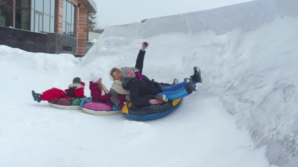 Thumbnail for Mom Dad and Children Ride a Tubing in the Winter