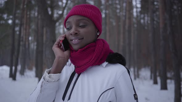 Thumbnail for Portrait Young African American Girl Talking By Cell Phone in Winter Forest Smiling Close Up