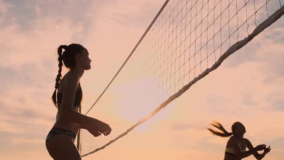 Thumbnail for Athletic Girl Playing Beach Volleyball Jumps in the Air and Strikes the Ball Over the Net on a