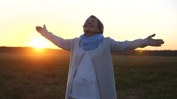 Thumbnail for Cheerful Senior Woman With Arms Outstretched To Sunset Sky Standing In Field