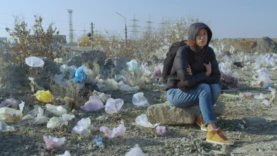 Thumbnail for A Girl Sits in a Place Contaminated with Plastic Bags. The Scale of the Planet s Pollution Is