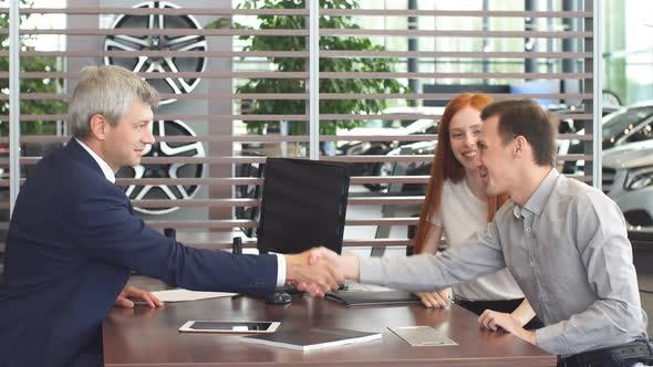 Thumbnail for Confident Mature Salesman or Manager Offering Car Purchase Contract To Young Couple.