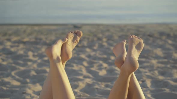 Thumbnail for Two Pairs of Slim Young Female Feet at the Background of Sandy Beach and Water. Unrecognizable