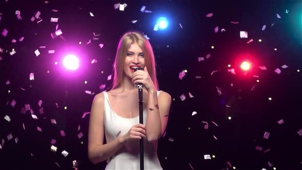 Cover Image for Blonde Girl Singing Into a Retro Microphone, Slow Motion