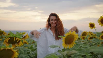 Happy Woman in the Field with Sunflowers
