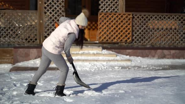 Thumbnail for Junge Frau Schaufeln Schnee auf Hinterhof in der Nähe des Hauses