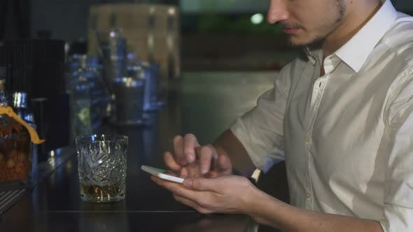 Thumbnail for Cropped Close Up of a Man Using His Smart Phone at the Bar While Having a Drink
