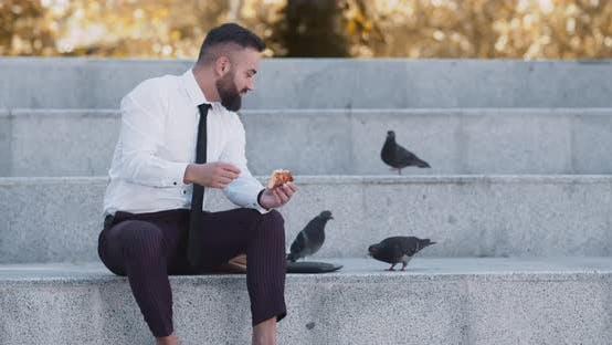Thumbnail for Happy Mature Businessman Feeding Pigeons with Pizza in Autumn Urban Park