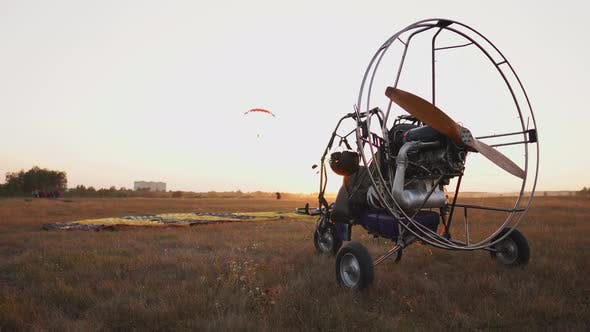 Thumbnail for Motor Paraglider Stands at the Airport in the Rays of Sunset Sunlight