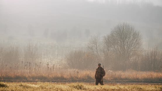 Thumbnail for Hunter in Hunting Equipment with Gun on his Shoulder Walks Through the Field Foggy Morning