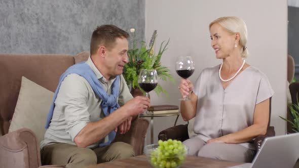 Thumbnail for Happy Middle-Aged Couple Relaxing in Armchairs at Home with Wine