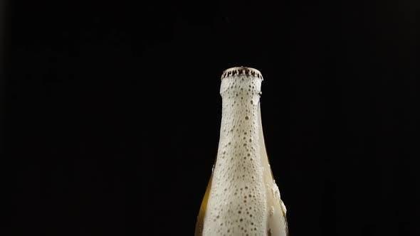 Thumbnail for Man schüttelt eine Flasche Bier. Bier beginnt mit Schaumstoffröm unter dem Deckel auszugießen