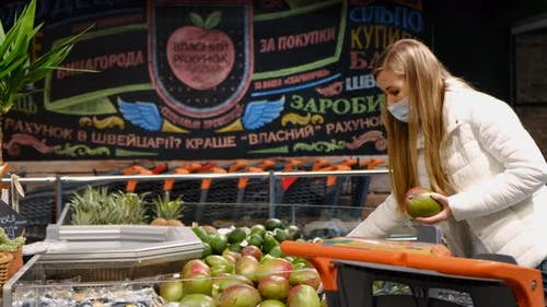 Young Woman Buys Mangoes at the Fruit Market