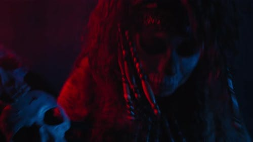 Female Shaman Is Conjuring with a Cane with Skulls on It Film Grain