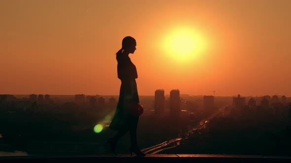 Woman Engineer Holding Helmet Outdoors Cityscape at Sunrise