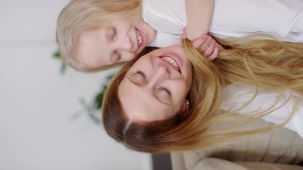Thumbnail for Vertical Video of Happy Girl Hugging and Kissing Mother