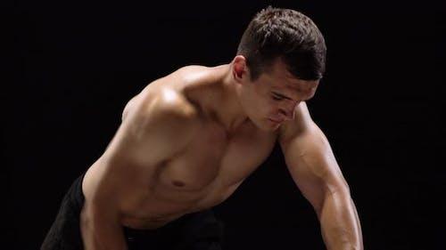 Mann beugt seine Hände mit Hanteln, die seinen Rücken auf einem schwarzen Hintergrund im Studio trainieren