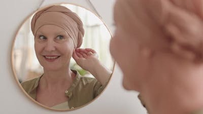 Smiling Lady in Headscarf Looking in Mirror