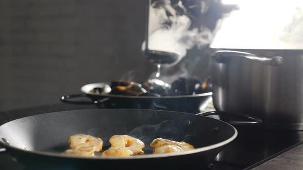 Thumbnail for Cooking in Restaurant Kitchen. Prawns Being Cooked in Frying Pan with Steaming Saucepan and Pan in