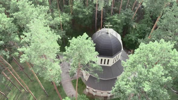 Drone flying over beautiful christian domed church surrounded by green trees in city park