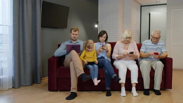 Thumbnail for Family Goes and Sits on the Couch with Personal Gadgets. Addicted To Modern Technology Phone Devices