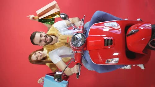 Happy Beautiful Couple on a Motorcycle Bought Gifts, the Woman Has a Bunch of Gift Bags in Her Hands