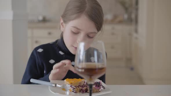 Thumbnail for Pretty Blond Girl Sitting at the Table in the Kitchen Eating Cake with Her Fingers