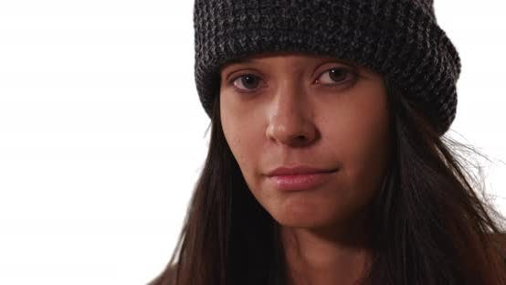 Thumbnail for Millennial girl in beanie making eye contact with camera on white background